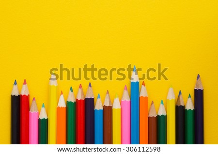 Colorful crayons organized in a row over yellow background, above view with copy space for text or other design