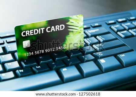 Colorful credit card on computer keyboard - stock photo