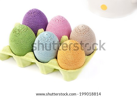 Colorful crocheted eggs in a light green carton egg box on a white background - stock photo