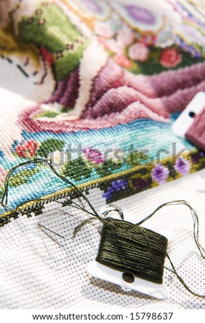 Colorful cross stitch art in the making, showing various color threads. - stock photo