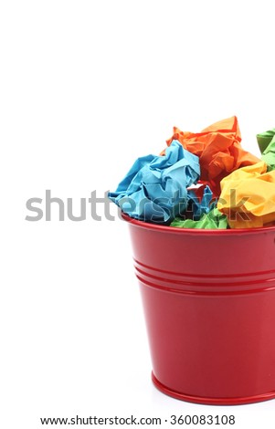 Colorful crumpled paper ball in pail on white background