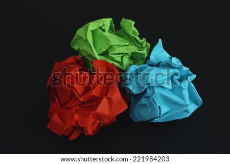 Colorful crumpled paper balls on a black background (Red, Green, Blue).