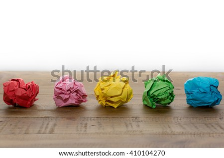 Colorful crumpled paper on a wooden table - stock photo