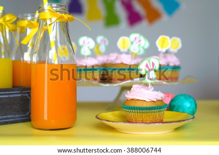 Colorful cupcake decorated with bunny picker on the yellow plate and orange juice in glasses in Easter scene  - stock photo