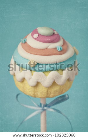 Colorful cupcake pops on blue background - stock photo
