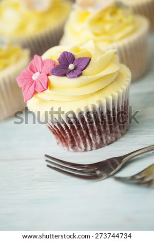 Colorful cupcake with sugar flower decoration - stock photo