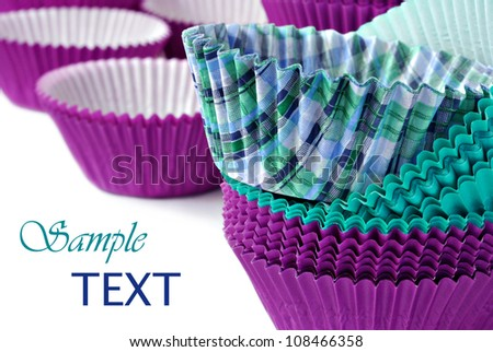 Colorful cupcake wrappers on white background with copy space.  Macro with shallow dof. - stock photo