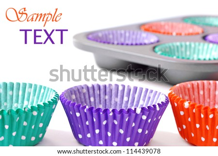 Colorful cupcake wrappers with baking pan on white background with copy space.  Macro with shallow dof. - stock photo