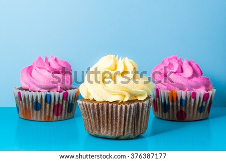 Colorful cupcakes against a blue background