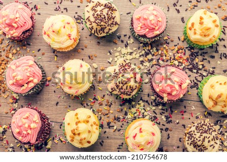 colorful cupcakes frosted with a variety of frosting flavors - stock photo