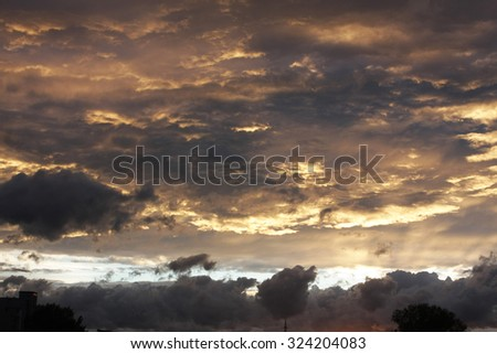 colorful dark dramatic clouds lit by yellow light