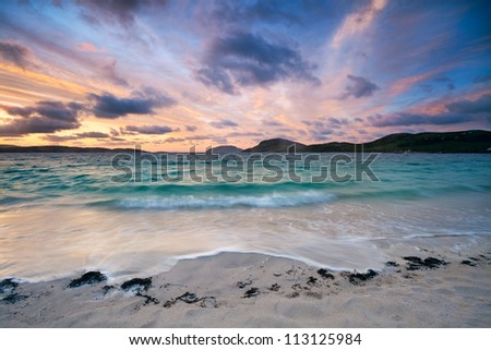Colorful dawn on a white sandy beach . Stunning sunrise over Vatersay beach, Outer Hebrides, Scotland . - stock photo
