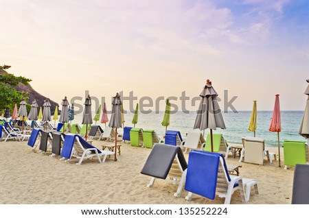 colorful deck chairs on the beach, sunrise time - stock photo