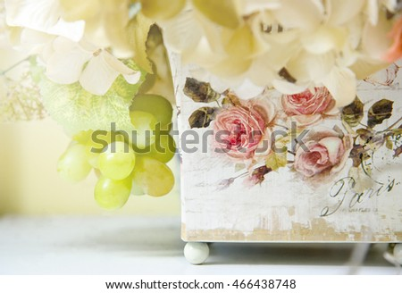 Colorful decoration artificial flower in decoupage wooden tree box, vintage style (soft focus)