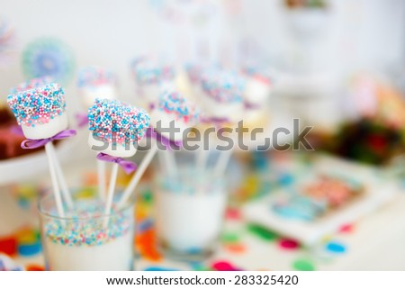 Colorful decoration of kids birthday party table with marshmallows and sweets - stock photo