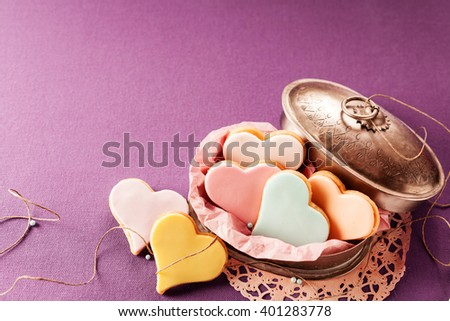 Colorful decorative iced heart shaped cookies symbolic of love and romance in a vintage tin, high angle view on a purple background with copy space for a greeting to your Valentines sweetheart - stock photo