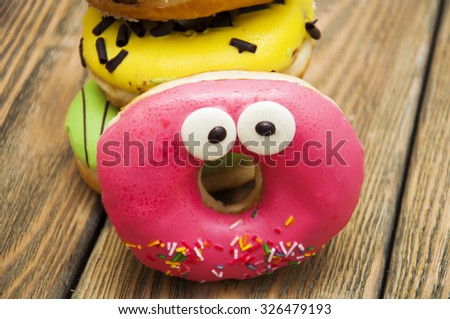 Colorful delicious donuts on a wooden background