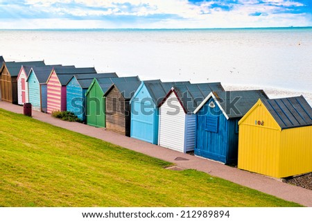 Colorful diagonal line of beach huts in England - stock photo
