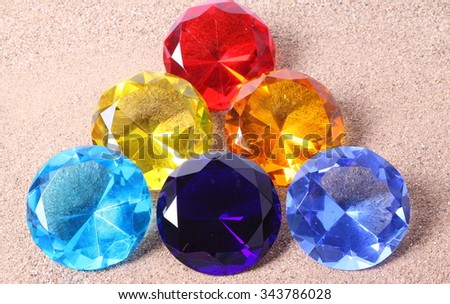 Colorful diamonds on sand background - stock photo