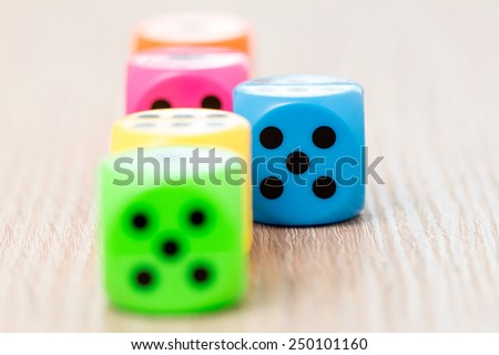 Colorful dice on the wooden surface. Selective focus on blue - stock photo
