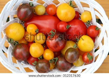 Colorful different kind tomatoes in white basket. - stock photo