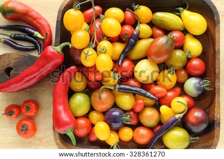 Colorful different kind tomatoes in wooden bowl. - stock photo