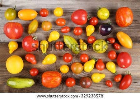 Colorful different kind tomatoes on wooden background. - stock photo