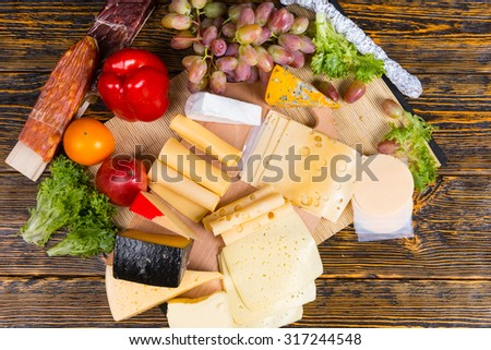Colorful display of different cheeses on a buffet table arranged in wedges and slices with fresh grapes, red bell pepper, tomato and olives, overhead view