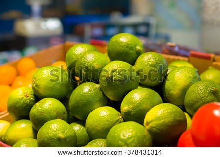 Colorful display of green limes and other vegetables and fruit in a Canadian grocery market