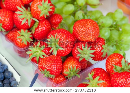 Colorful display of strawberries at a food market.