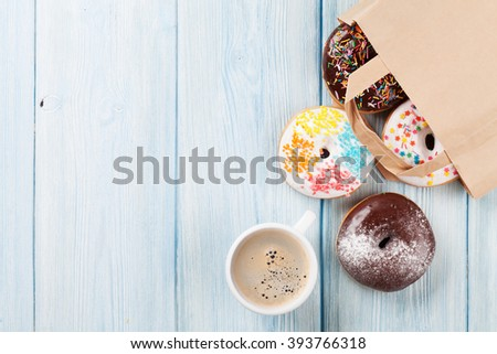 Colorful donuts in paper bag and coffee cup on wooden table. Top view with copy space - stock photo