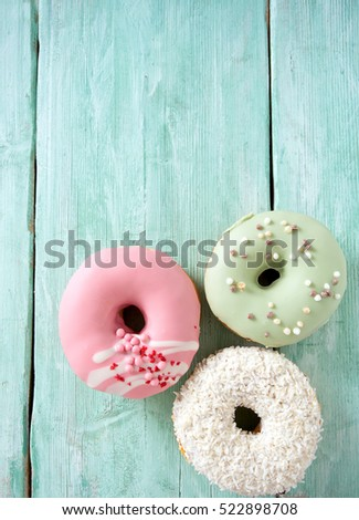 colorful doughnuts on turquoise wooden surface