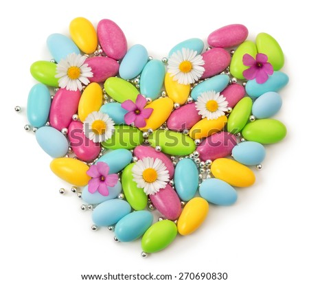 colorful dragees and wildflowers in shape of heart - stock photo