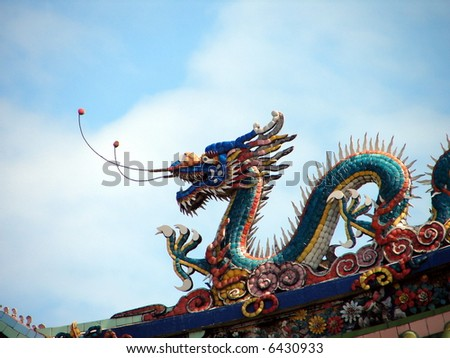 Colorful Dragon on the roof of oriental temple, against blue sky