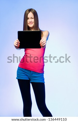 Colorful dressed expressive teen beauty holding tablet computer for copy space. - stock photo