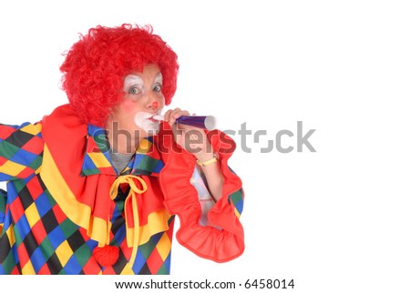 Colorful dressed female holiday clown blowing toy horn blower, happy joyful expression on face