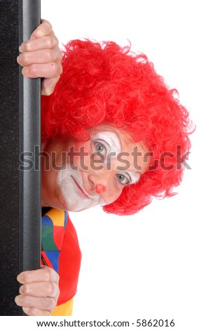 Colorful dressed female holiday clown peeping around corner, happy joyful expression on face