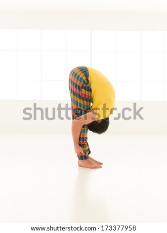 Colorful dressed male repeating Uttanasana yoga exercises in a white room with window background