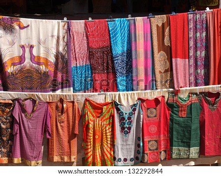 colorful dresses  scarfs and shirts on the open market in India - stock photo