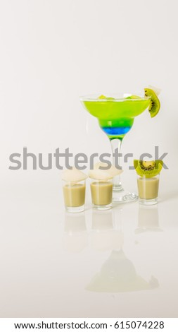 Colorful drink in a margarita glass, blue and green combination, many drinks in a shotglass, party set