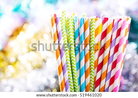 Colorful drinking striped straws on colorful background