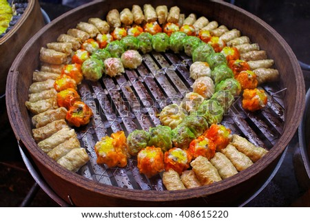 Colorful dumplings in wooden bowl, chinese steamed dumpling in bamboo steamer in chinese restaurant, chinese street food, tasty street food, dumplings set, dumplings assortment, canton cuisine, China - stock photo