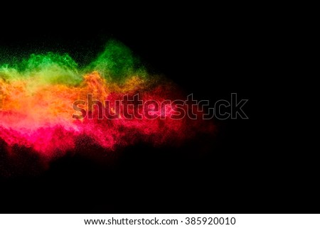 Colorful dust particle explosion over black background. Closeup of a color explosion isolated on black - stock photo
