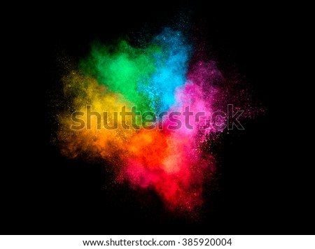 Colorful dust particle explosion resembling a pyrotechnic effect over black background. Closeup of a color explosion isolated on black - stock photo