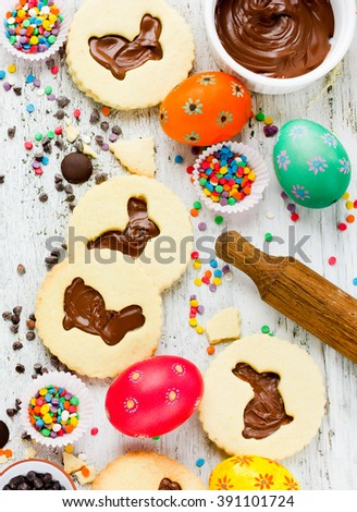 Colorful Easter baking background cookies bunny with chocolate eggs sprinkling top view - stock photo