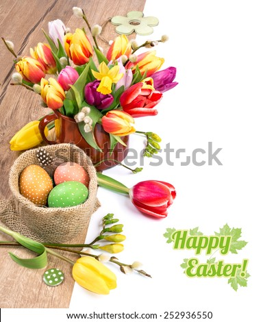 Colorful Easter border with bunch of tulips and Easter eggs on wood, white background, deep DOF, space for your text - stock photo