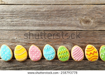 Colorful easter cookies on grey wooden background - stock photo
