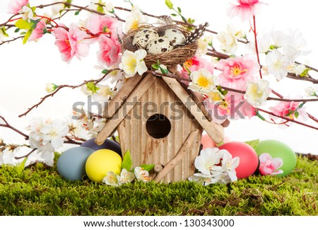 colorful easter decoration with birdhouse and eggs on green grass. spring apple and cherry blossoming