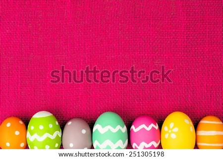 Colorful Easter egg bottom border over a pink burlap background - stock photo