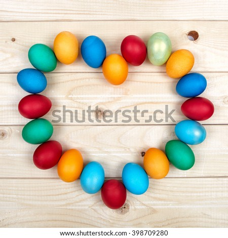 Colorful Easter egg frame on light wooden boards. A heart-shaped figure of hand painted eggs